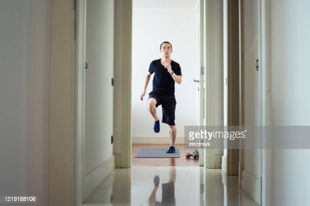 millennial man exercising at home - cardiovascular exercise stock pictures, royalty-free photos & images