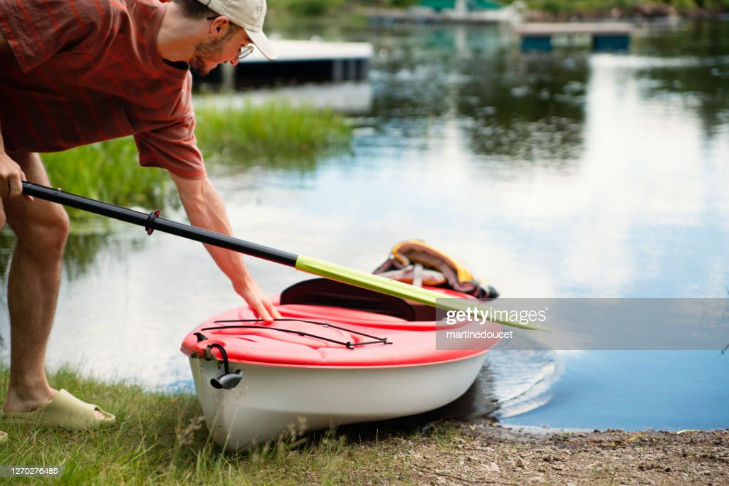 Millennial man going kayaking on country lake. : Stock Photo