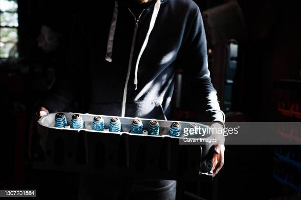 millennial man in garage holding a motor head in his hands in sunlight - grimes musician stock pictures, royalty-free photos & images