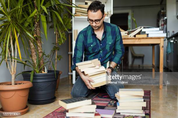 millennial man organizing his book collections - arrangement stock pictures, royalty-free photos & images