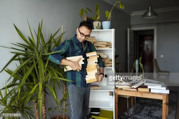 uomo millenario che organizza le sue collezioni di libri - arrangiare foto e immagini stock