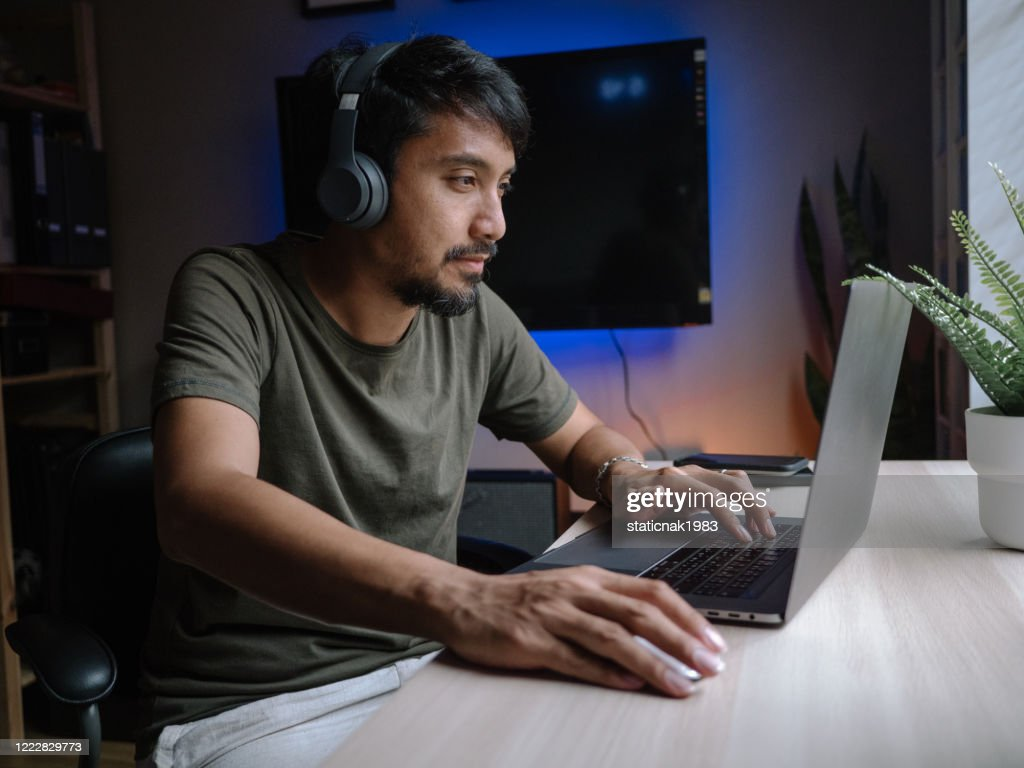 Millennial man playing computer game on laptop at home. : Stock Photo