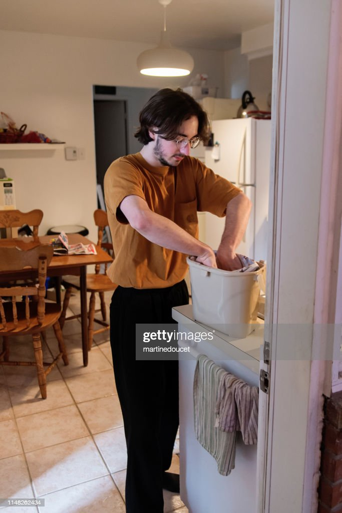 Millennial man putting newspaper in compost bin. : Stock Photo