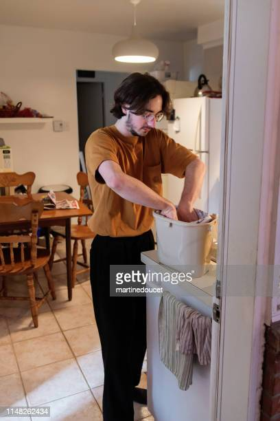 """millennial man putting newspaper in compost bin. - """"martine doucet"""" or martinedoucet stock pictures, royalty-free photos & images"""