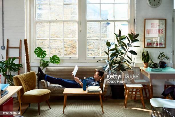 millennial man reclined on sofa using laptop - one mid adult man only stock pictures, royalty-free photos & images