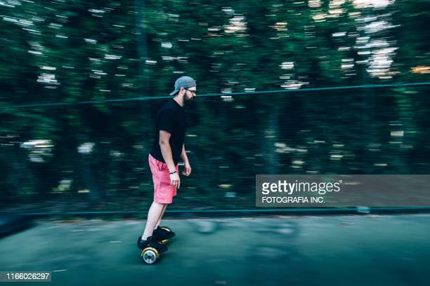 millennial man riding hover board - hoverboard stock pictures, royalty-free photos & images