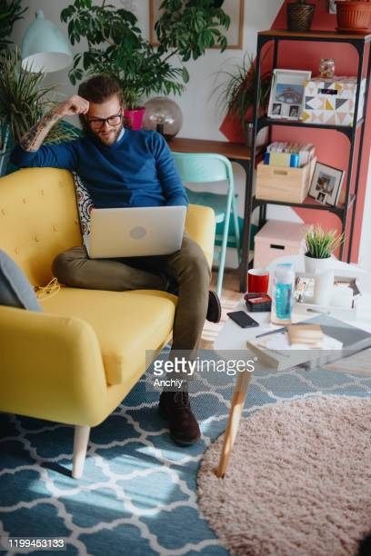 millennial man shopping online - surfing the net stock pictures, royalty-free photos & images
