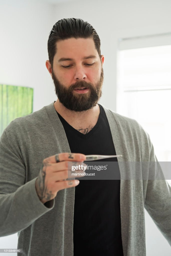 Millennial man taking temperature while in quarantine isolation Covid-19 : Stock Photo