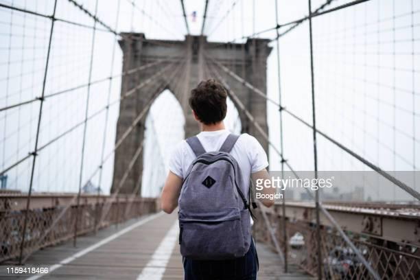 millennial man with backpack walking across the brooklyn bridge - brooklyn new york imagens e fotografias de stock