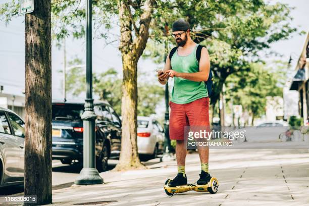 millennial man with hover board - hoverboard stock pictures, royalty-free photos & images