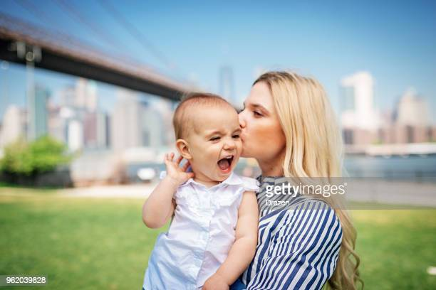 Millennial mother kissing her cute baby girl