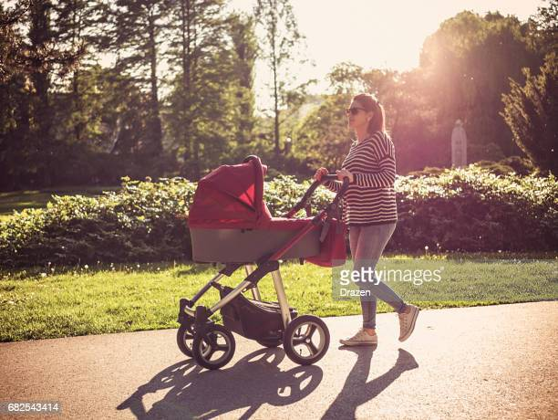 Millennial mother pushing prams with newborn baby