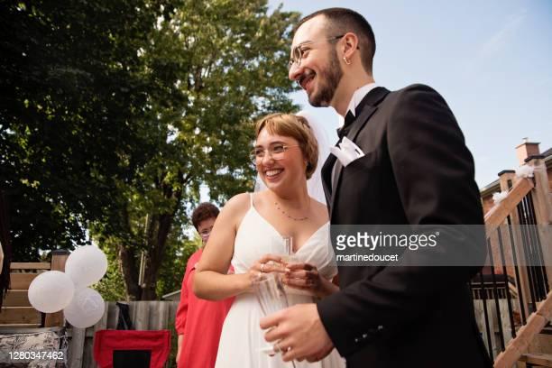 """millennial pareja recién casado en el cóctel de bodas en el patio trasero. - """"martine doucet"""" or martinedoucet fotografías e imágenes de stock"""