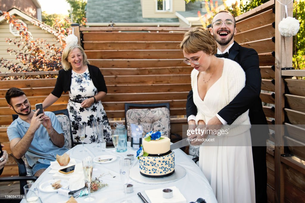 Millennial newlywed couple cutting cake at wedding cocktail in backyard. : Stock Photo
