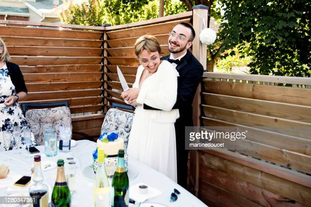 """millennial newlywed couple cutting cake at wedding cocktail in backyard. - """"martine doucet"""" or martinedoucet stock pictures, royalty-free photos & images"""