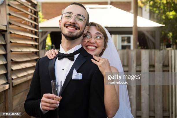 """millennial pareja recién casado posando en cóctel de boda en el patio trasero. - """"martine doucet"""" or martinedoucet fotografías e imágenes de stock"""
