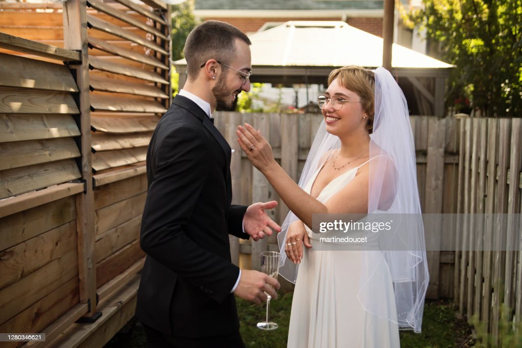 Millennial newlywed couple posing at wedding cocktail in backyard. : Stock Photo