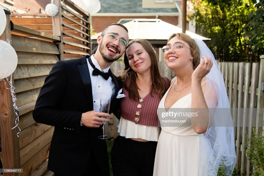 Millennial newlywed couple posing with bridesmaid in backyard. : Stock Photo