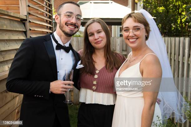 """millennial newlywed couple posing with bridesmaid in backyard. - """"martine doucet"""" or martinedoucet stock pictures, royalty-free photos & images"""