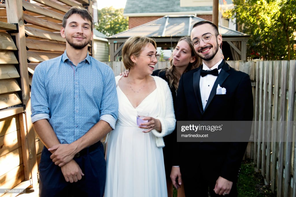 Millennial newlywed couple posing with brother and sister in backyard. : Stock Photo