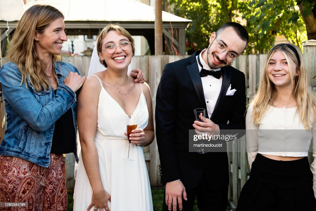 Millennial newlywed couple posing with family members in backyard. : Stock Photo