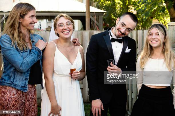 """millennial newlywed couple posing with family members in backyard. - """"martine doucet"""" or martinedoucet stock pictures, royalty-free photos & images"""