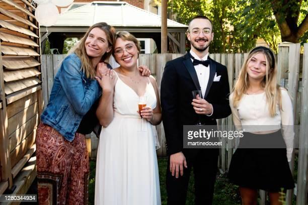 """millennial recién casado pareja posando con miembros de la familia en el patio trasero. - """"martine doucet"""" or martinedoucet fotografías e imágenes de stock"""