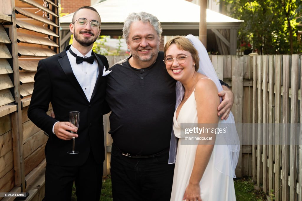Millennial newlywed couple posing with father of the bride in backyard. : Stock Photo