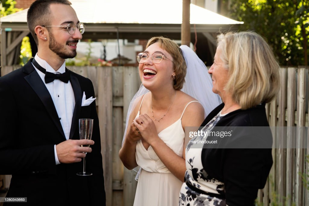 Millennial newlywed couple posing with grandmother in backyard. : Stock Photo