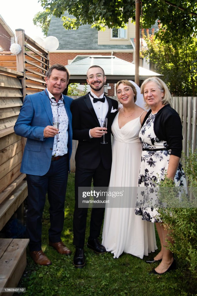 Millennial newlywed couple posing with grandparents in backyard. : Stock Photo