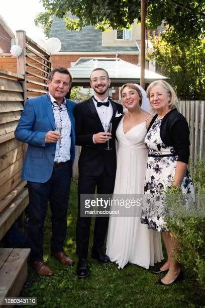 """millennial recién casado pareja posando con abuelos en el patio trasero. - """"martine doucet"""" or martinedoucet fotografías e imágenes de stock"""