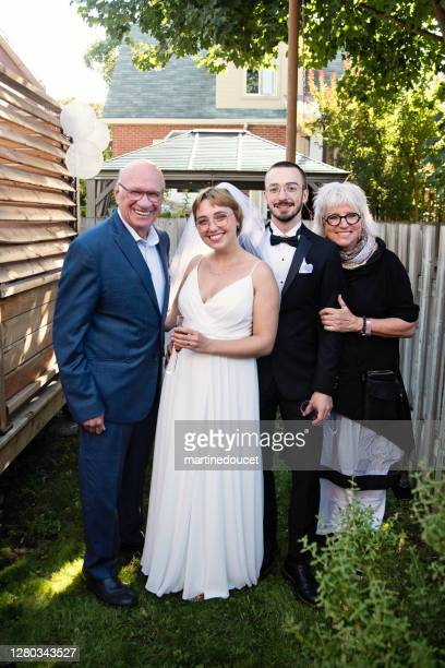 """millennial newlywed couple posing with grandparents in backyard. - """"martine doucet"""" or martinedoucet stock pictures, royalty-free photos & images"""