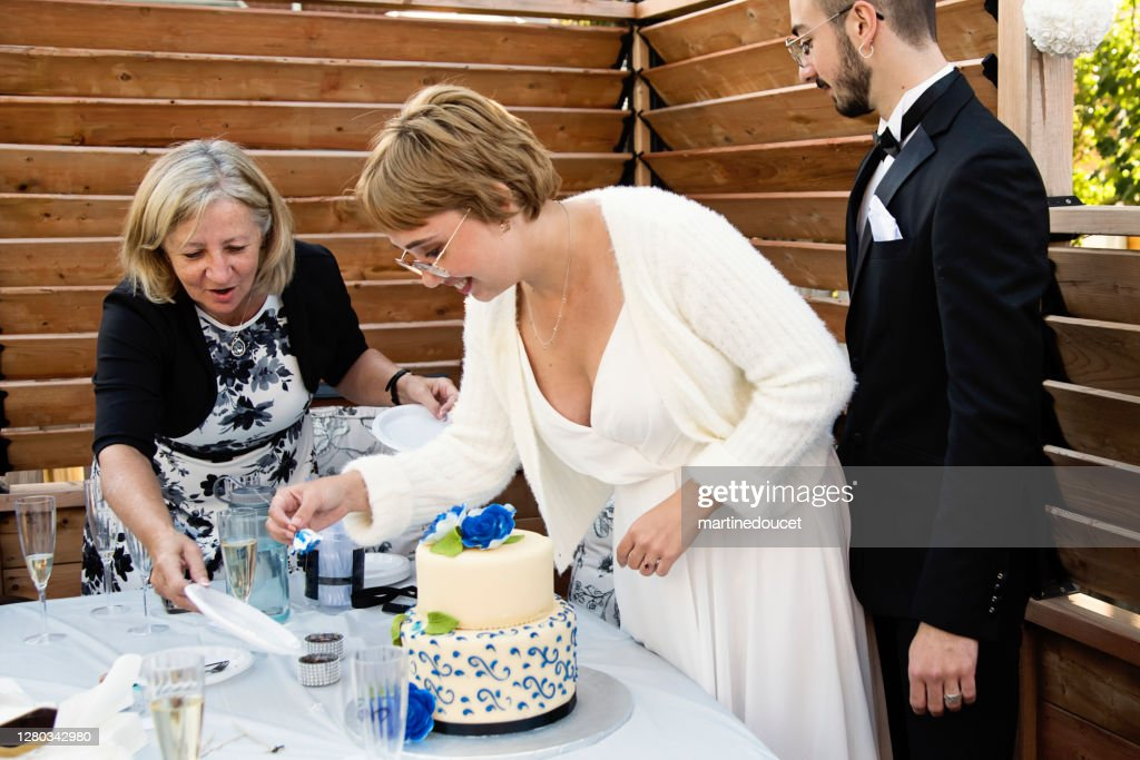 Millennial newlywed couple serving cake at wedding cocktail in backyard. : Stock Photo