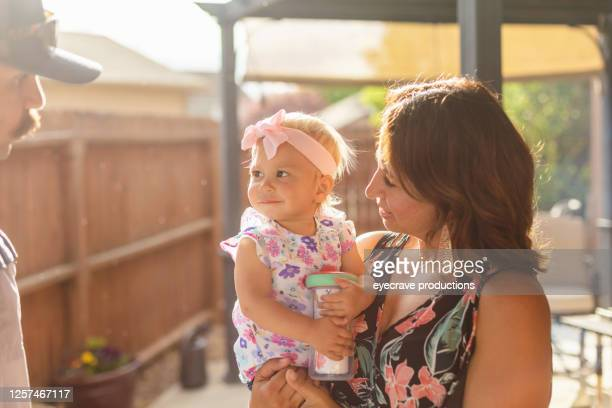 millennial parents with mother holding female toddler daughter outdoors on patio - eyecrave  stock pictures, royalty-free photos & images