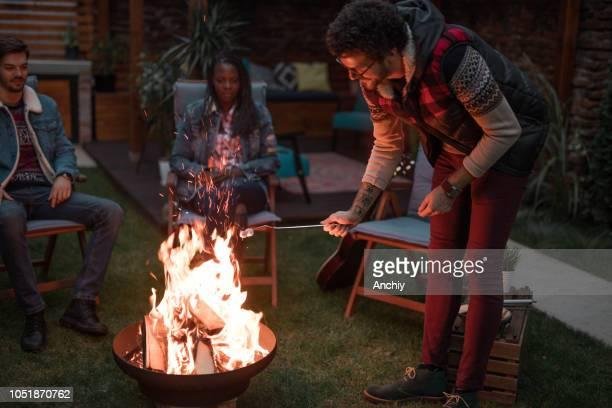 Millennial roasting marshmallows on fire pit