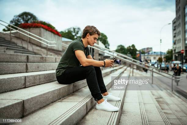 millennial scandinavian using phone and sitting on the stairs - nordic countries stock pictures, royalty-free photos & images