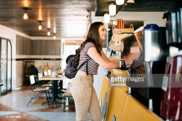 Millennial woman at ordering Coffee shop counter