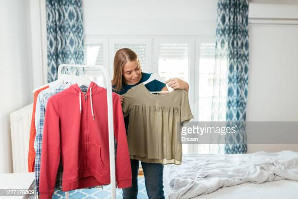 millennial woman choosing and arranging clothes from rack in bedroom - top capo di vestiario foto e immagini stock
