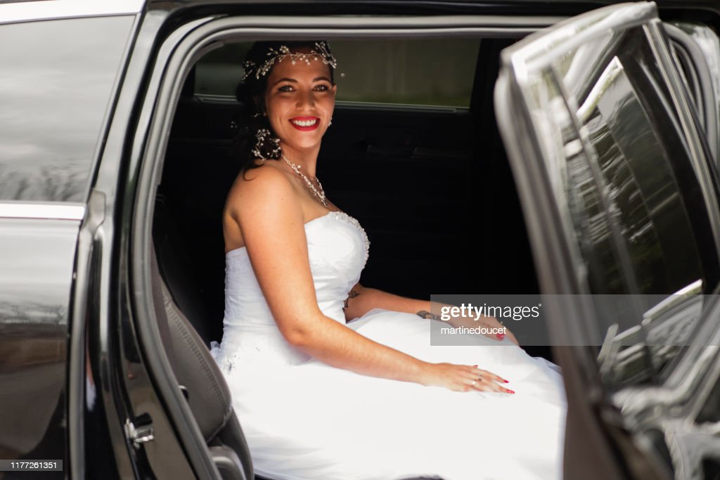 Millennial woman getting in limousine for her wedding. : Stock Photo
