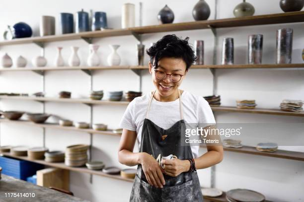 millennial woman in her ceramics shop - ceramics stock pictures, royalty-free photos & images
