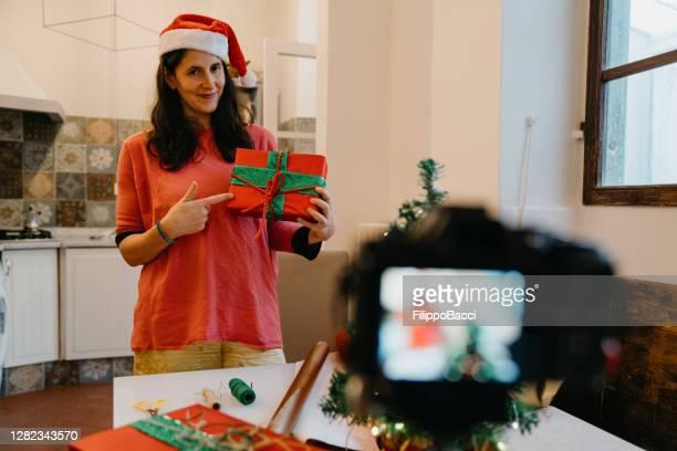 influenceur femme millénaire enregistrement d'une vidéo d'un tutoriel: comment faire la boîte cadeau parfaite - une seule femme d'âge moyen photos et images de collection
