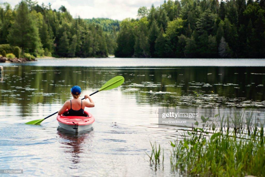 Millennial woman kayaking on country lake. : Stock Photo
