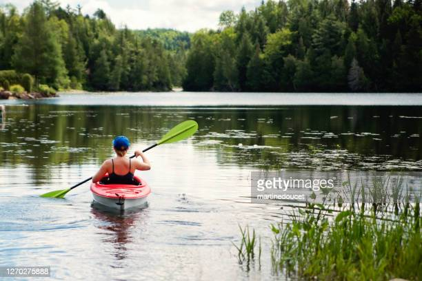 """millennial woman kayaking on country lake. - """"martine doucet"""" or martinedoucet stock pictures, royalty-free photos & images"""