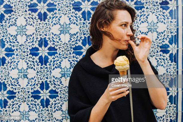 millennial woman licking finger while eating ice cream at a tiled wall - lissabon stock-fotos und bilder