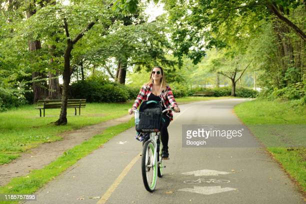 millennial woman on vacation riding a bike on a path in stanley park vancouver canada - bicycle lane stock pictures, royalty-free photos & images