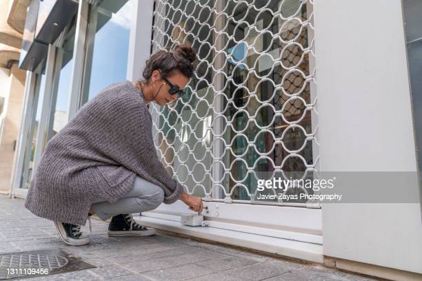 millennial woman openning a small business security grill - opening event stock pictures, royalty-free photos & images