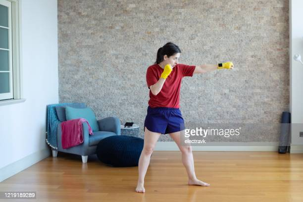 millennial woman practicing martial arts at home - martial arts stock pictures, royalty-free photos & images