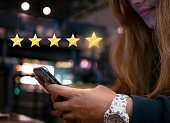 Millennial woman submitting star rating feedback on mobile device after internet shopping experience