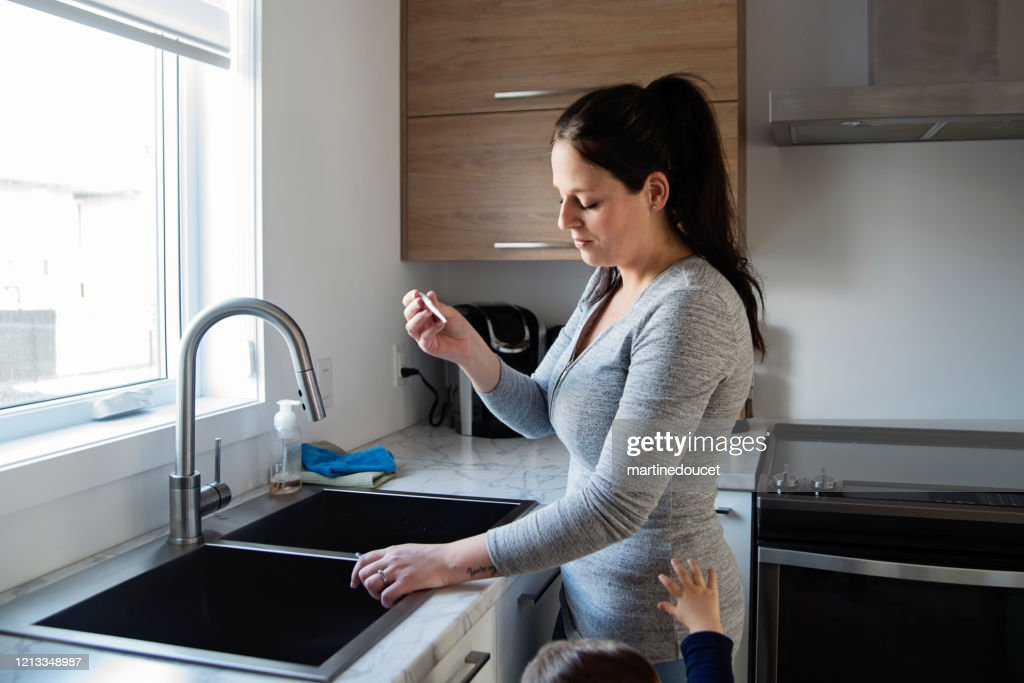 Millennial woman taking temperature while in quarantine isolation Covid-19 : Stock Photo