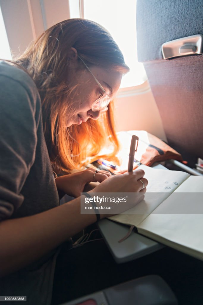 Millennial woman travelling alone in plane. : Stock Photo